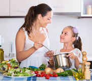 Woman and little girl cooking vegetables. Portrait of russian women and little girl cooking vegetables Stock Image