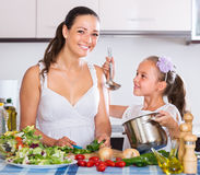 Woman and little girl cooking vegetables. Portrait of spanish women and little girl cooking vegetables Royalty Free Stock Photo