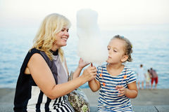 Woman and little girl eating a cotton candy Stock Photo