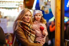 Woman and little girl eating crystalized apple on Christmas mark Stock Photography