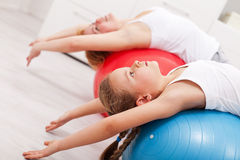 Woman and little girl exercising Stock Photography