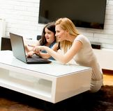 Woman and little girl in front of a laptop computer stock image