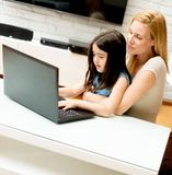 Woman and little girl in front of a laptop computer stock images