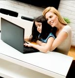 Woman and little girl in front of a laptop computer royalty free stock images