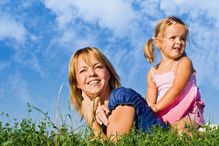 Woman and little girl in the grass Stock Photos