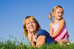 Woman and little girl in the grass Stock Image