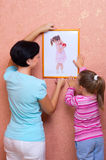Woman with little girl hang up a picture Royalty Free Stock Image