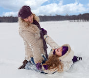 Woman and little girl having fun in the snow Stock Image
