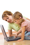 Woman and little girl with laptop Stock Images