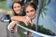 Woman and little girl looking out by car window Royalty Free Stock Image