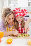 Woman and little girl making fresh fruits snack Stock Images