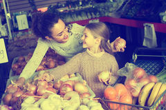Woman and little girl at market. Smiling young women with little daughter buying vegetables in grocery food store Royalty Free Stock Image