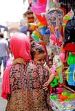 Woman with little girl in medina of Essaouira. Essaouira Morocco A woman with pink veil and colored dress takes her daughter`s shoulder walk through the shops of Royalty Free Stock Images