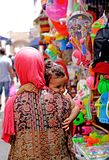 Woman with little girl in medina of Essaouira. Ssaouira Morocco A woman with pink veil and colored dress takes her daughter`s shoulder walk through the shops of Stock Photo