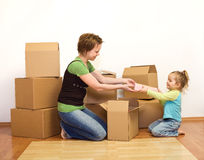 Woman and little girl in a new home unpacking Stock Photo