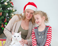 Woman and little girl playing with cat Royalty Free Stock Photo