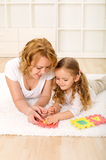 Woman and little girl playing on the floor Royalty Free Stock Photo