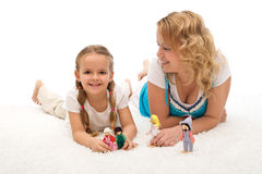 Woman and little girl playing on the floor Stock Photos
