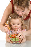 Woman and little girl preparing fruit salad Stock Photos