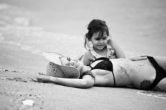 Woman and little girl relaxing on the beach stock photos
