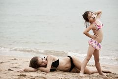 Woman and little girl relaxing on the beach stock images