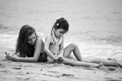 Woman and little girl relaxing on the beach. Thailand stock photos