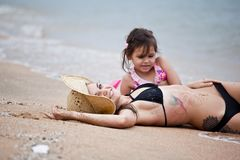Woman and little girl relaxing on the beach. Thailand stock image