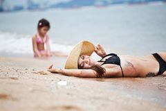 Woman and little girl relaxing on the beach stock photography
