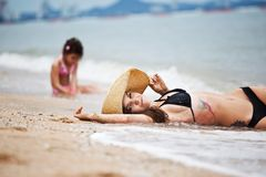Woman and little girl relaxing on the beach royalty free stock photography