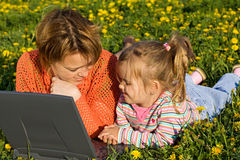 Woman and little girl relaxing on the flower field Royalty Free Stock Photo