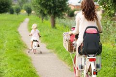 Woman and little girl riding bikes in park. Rear view portrait of women and little girl riding bikes in park Royalty Free Stock Photography