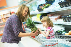 Woman and little girl shopping fruits royalty free stock images
