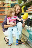 Woman and little girl shopping fruits stock images