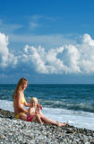Woman and little girl sit on seacoast Stock Photography