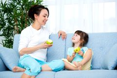 Woman and little girl sitting on comfortable couch at home. Young mother talking communicates with small daughter. Best friends,. Happy motherhood stock photo
