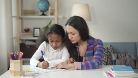 Woman and little girl is sitting at table and doing school homework together. stock footage