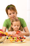 Woman and little girl slicing fruits Royalty Free Stock Image