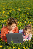 Woman and little girl on the spring flower field Royalty Free Stock Photos