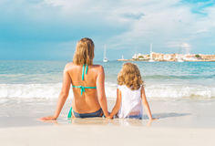 Woman and little girl sunbathing. Stock Images
