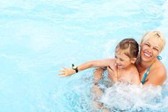 Woman and  little girl swimming. Smiling middle-aged women and  little girl swimming in a pool with blue water and hydro massage Stock Images