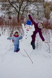 Woman and little girl and their funny snowman winter snow Royalty Free Stock Image