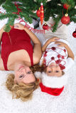 Woman and little girl under the christmas tree Stock Photos