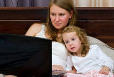 Woman and little girl watching cartoons on laptop Royalty Free Stock Photos