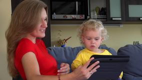 Woman with little girl waving hands looking at tablet computer. stock video