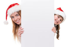 Woman and little girl wearing Santa Claus hat. Young women and little girl wearing Santa Claus hat and looking out white board Stock Image
