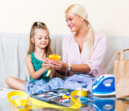 Woman and little girl working. Cheerful blonde mother and little daughter working with textile indoors Royalty Free Stock Image