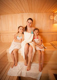 Woman with little girls relaxing at finnish sauna Royalty Free Stock Photography