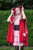 Woman with little red riding hood costume in park at cosplay exhibition event Royalty Free Stock Images