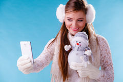 Woman with little snowman taking selfie photo. Stock Photos