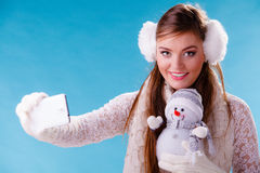 Woman with little snowman taking selfie photo. Royalty Free Stock Photos